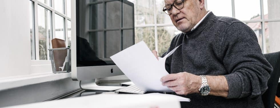 En mand, der kigger i nogle mapper og i nogle papirer.