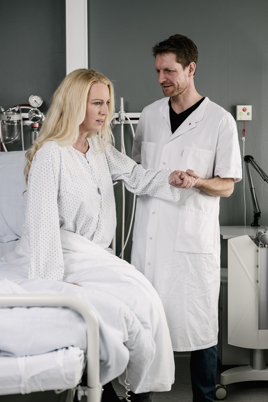 En patient, der bliver hjulpet ud af sengen af sin læge.